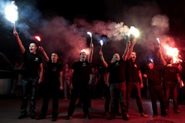 Apoiantes da Aurora Dourada com chamas em riste em Thessaloniki, Grécia no dia das eleições de 6 de Maio, em que o partido ganhou 7% dos votos. Foto de Alexandros Michailidis © Copyright Demotix
