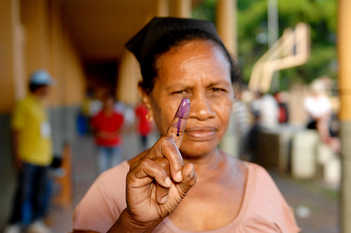 An East Timorese woman holds up her stained finger after voting. Photo by United Nations Photo (CC BY-NC-ND 2.0)
