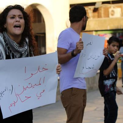 A woman protestor in Ben Ghazi holding a sign which reads Leave the dead and the living alone!