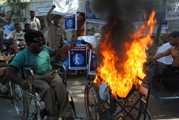 Disabled protesters set a wheelchair on fire during demonstrations against social welfare cuts