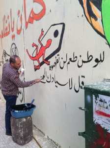 Artists painting murals on Mohamed Mahmood Street in Cairo after police erased them
