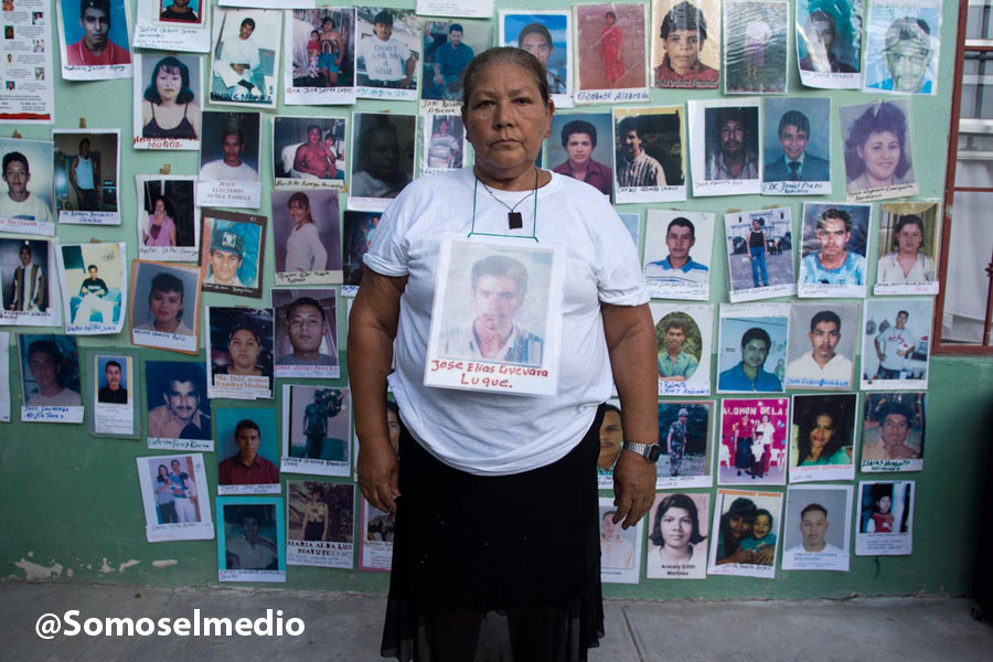 Mother participating in the caravan stands in front of photos of missing migrants.