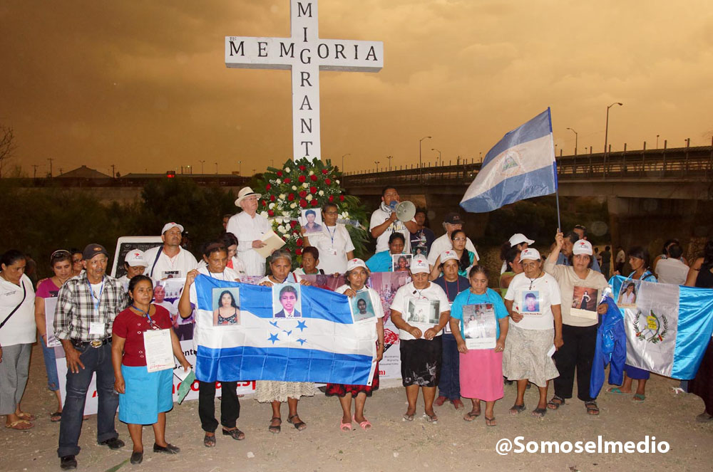Central American mothers participating in the caravan make and offering at a cross in memory of the migrants.