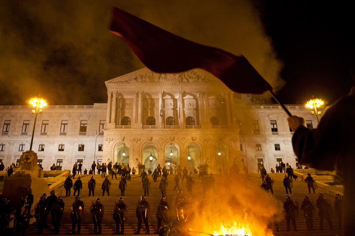 """Riot police monitor protests as a fire burns in front of the parliament building as demonstrations take place over government imposed austerity measures designed to ease Portugal's economic and financial crisis"". Photo by João Caetano copyright Demotix (15/10/2012)"