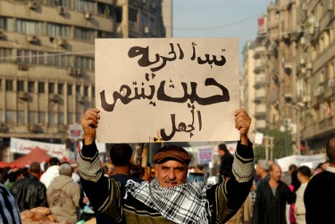 A man carries a poster which reads: Freedom starts where ignorance ends