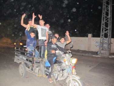 Boys race through Gaza City celebrating the ceasefire