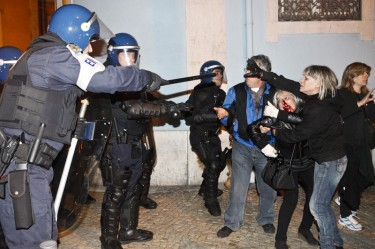 Police men point batons while a woman is bleeding from the nose during the chashes. Photo by Pedro Nunes copyright Demotix (14/11/2012)