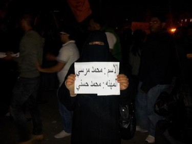 A protestor carries a sign which reads [ar]: Name: Mohammed Mursi; Profession: Mohammed Hosni