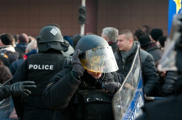 Policeman in Skopje, Macedonia, wipping splashed egg from helmet.