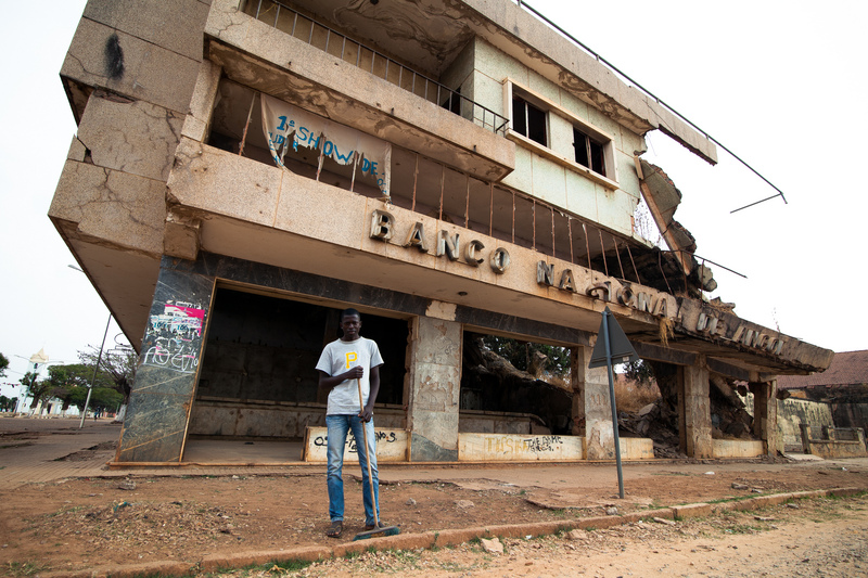 A guy stands in front of the remnants of a collapsed building of the National Bank of Angola in Kamacupa (Bi Province), destroyed during the civil war. There are people still living inside. -- The civil war in Angola, that started in 1975, ended in 2002. Ten years later, in 2012, Angola is growing fast, though wounds from the recent conflict still remains. Photo by Bruno Abarca copyright Demotix (23/08/2012)