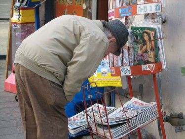 Elderly man checks the headlines in Tel Aviv, Israel.