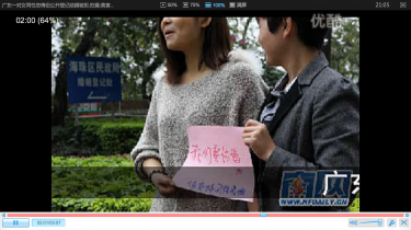 "A lesbian couple holding a sign that says ""we want to get married."" (A screenshot from youku)"