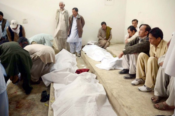 People gather near the dead bodies of victims, who were gunned down by unidentified armed men at the Scrap Market on Sarki Road in a target killing. Quetta, Pakistan. 16th October 2012  Image by PPPIimages. Copyright Demotix