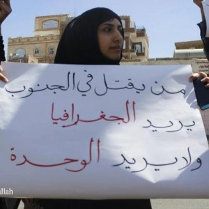 "A protester holding a placard that reads in Arabic ""He who is killing in the south wants the geography and does not want the unity"""