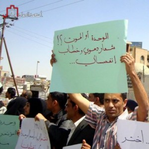 "A protester holding a sign that reads in Arabic ""unity or death is a bloody slogan and a separatist speech."""