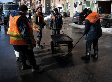Five road workers are patching a pothole in Kyiv, Ukraine. Photo by Sergii Kharchenko, copyright © Demotix (5/02/13).