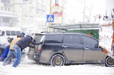 Kyiv residents help push a car stuck in the snow. Photo by jonatha borzicchi, copyright © Demotix (22/03/13).