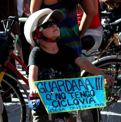 "Image by Gianluca Casanova from Facebook (CC). Child during demonstration in Montevideo, Uruguay.  Sign says: ""Watch ooout! because I don't have a bike line. Critical Mass Montevideo"""