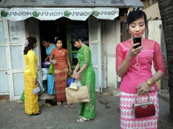 College graduates in Maiktila, Myanmar leaving a beauty salon. Image by Geoffrey Hiller. Used with permission
