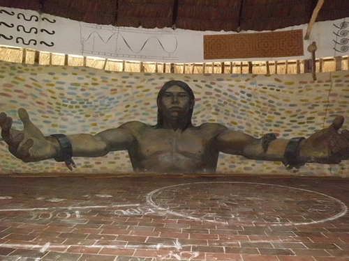 "A mural of ""Kiwxi"" an indigenous leader assassinated in Brazil and whose image adorns the inside wall of the churuata. Photo by Akaneto."