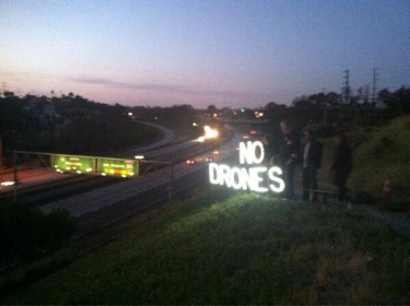 No Drones sign in neon overlooking a highway in San Diego (shared via twitter by Rooj Alwazir)