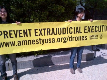 Sign held by Amnesty International members outside Senate drone wars hearing bulding via @andreaprasow
