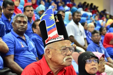 A supporter of the ruling party listens to the speech of the Prime Minister. Photo by Asyraf rasid, Copyright @Demotix (4/6/2013)