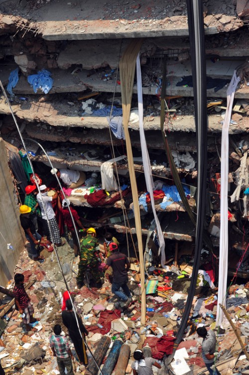 The crumbled roof of the factory. Many workers trapped in pockets inside. Image by Firoz Ahmed. Copyright Demotix (26/4/2013)