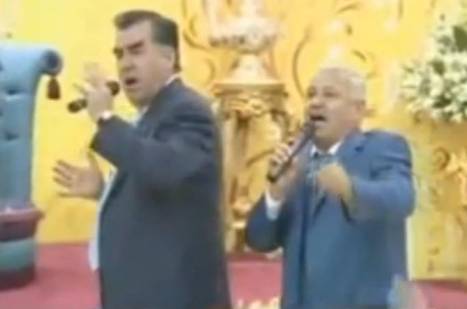 Rahmon (left) performs at his son's wedding. Screenshot from video uploaded by PolitikTJ