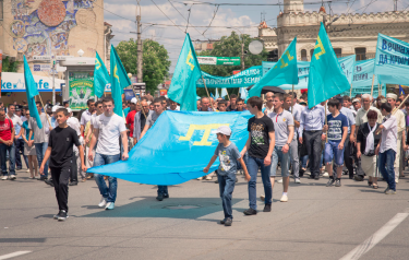 Crimean Tatar men carry their national flag at the May 18 commemoration of the 1944 Crimean Tatar deportations. Photo by Andy Ignatov (used with permission).