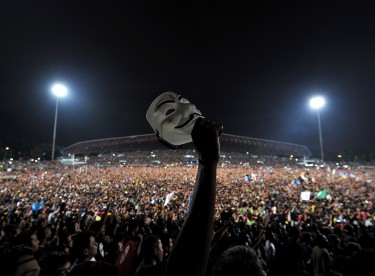 "A protester holds up an ""anonymous"" mask during an opposition coalition rally. Photo by Hafzi Mohamed, Copyright @Demotix (5/8/2013)"
