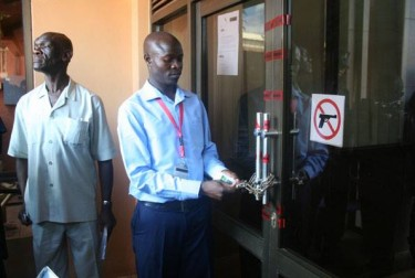 Head Of security at Daily Monitor opens the door after the reopening. Photo from Daily Monitor official Facebook page
