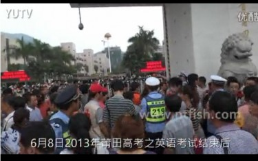 Anxious parents wait outside the exam site in China's eastern Fujian province( Screen grab from Youku .)