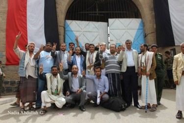Yemen's Revolution's Youth and supporting activists pose in front of Sanaa's central prison after their release
