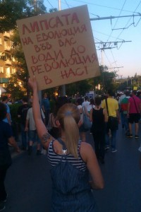 "A protester in Sofia carries a sign saying: ""The lack of evolution in you leads to a revolution in us!"" (Photo used with permission)"