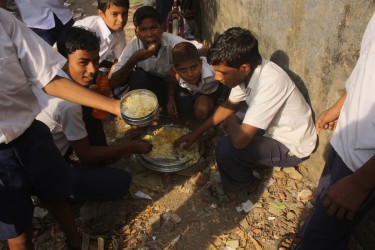 Students of a Hindi school in Mumbai eat on ground with seating arrangement or provision of plates.