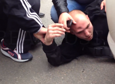 Anton Kudriashov lies in the road after being attacked, 27 July 2013, screenshot from YouTube.