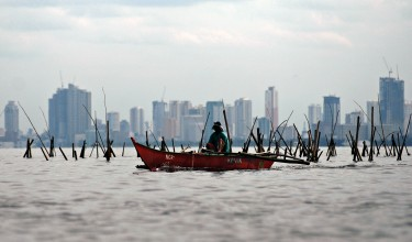 A fisherman gathers mussels on the waters of Manila Bay. Photo by Ezra Acayan, Copyright @Demotix (7/14/2013)