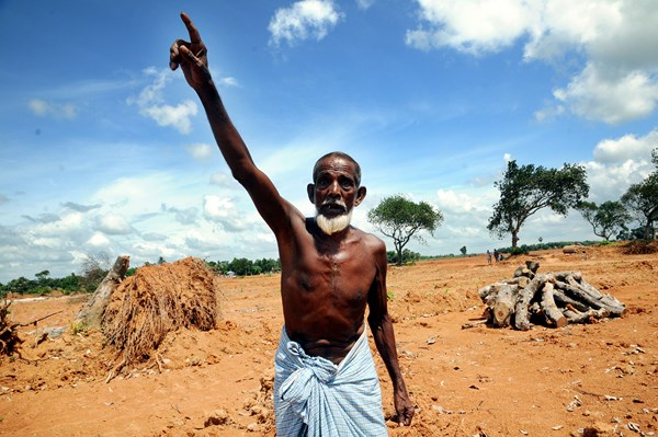 A man who lives on the land shouts at the governments decision to flatten the land destroying trees for a housing project. Image by Sanaul Haque. Copyright Demotix (5/8/2013)