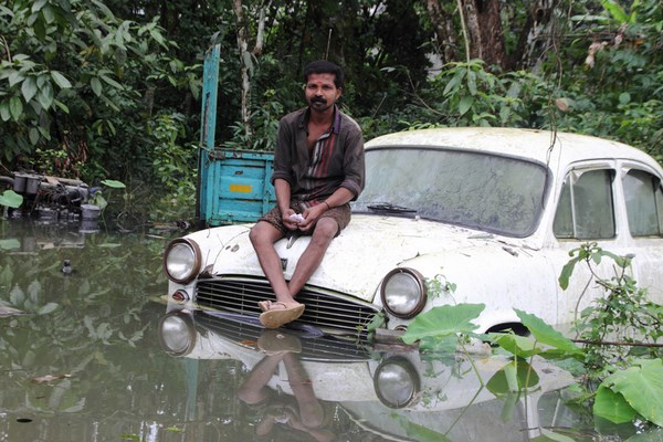 In South Kerla an unidentified man sitting on a car submerged in flood water