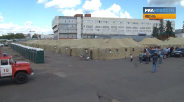 The detention center consists of tents on bare asphalt. YouTube screenshot.