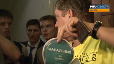 A Just Russia deputy demonstrates a pro-Navalny sticker found at the activist flat. YouTube screenshot.
