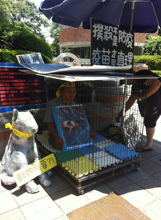 An animal right activist locked himself in an animal cage outside Council of Agriculture against the killing of stray dogs and cats to prevent the spread of rabies. He advocates for vaccination. Photo from 張敬偉 Facebook.