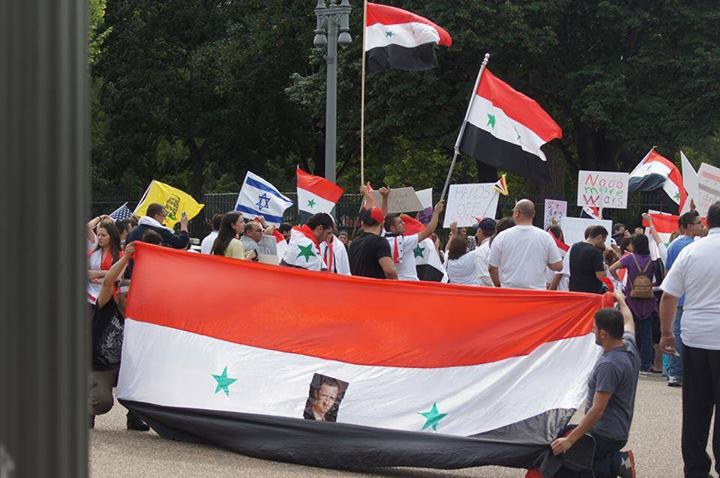 A pro-Assad protest in Washington DC. In addition to waving the Syrian flag, an Israeli flag is seen among the crowd. Photograph shared by Eiad Charbaji on his public Facebook page