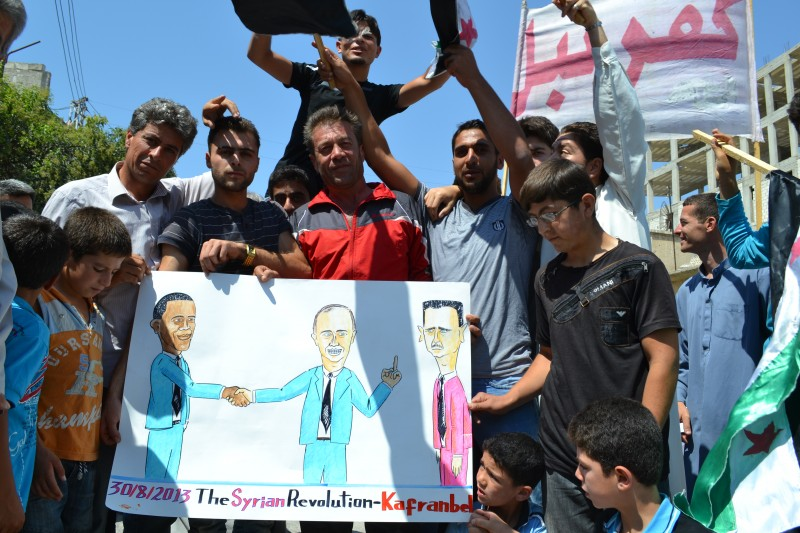 Syrian protesters carry banners calling for international action against the Assad regime in Kafranbel, Idlib, in northern Syria. Image by Majid Almustafa. Copyright Demotix August 30, 2013
