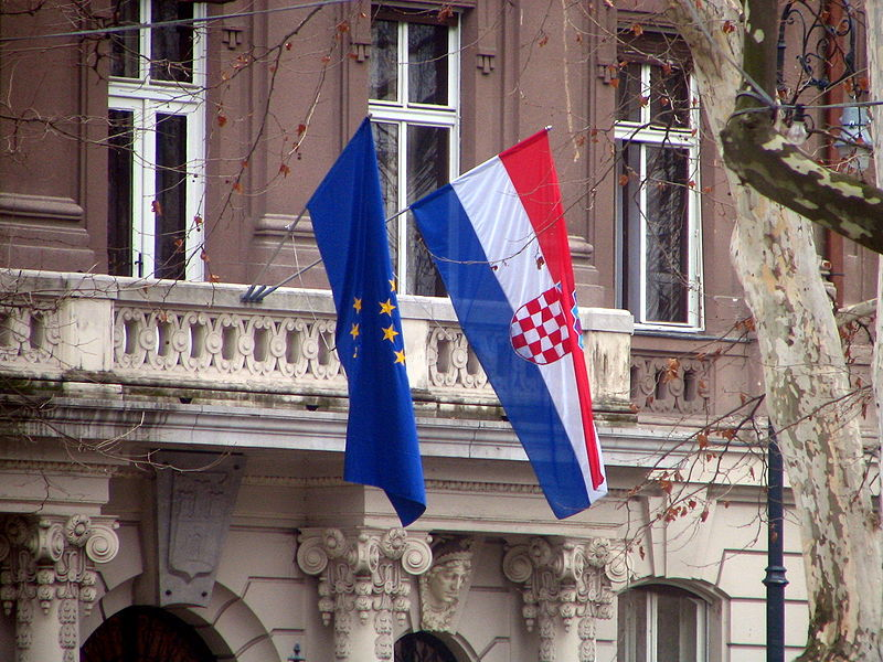 The Croatian and EU flags on a Croatian government building; photo by Bogdan Giusca, used under Creative Commons Attribution 3.0 license.