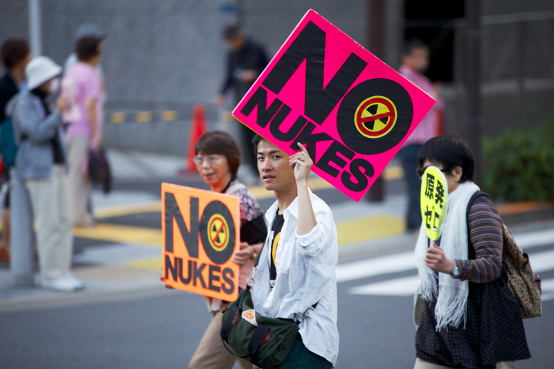 Protesters hold signs against nuclear power on the streets of Tokyo. The population's concerns over nuclear power in Japan have increased after the radioactive spill in Fukushima.<br /> Photo by KAZUMAC, copyright (c) Demotix (October 13, 2013)