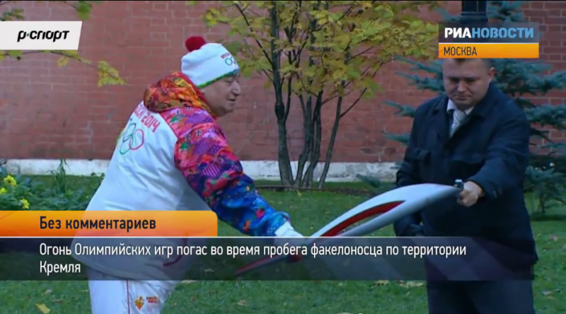 A guard lights the Olympic torch with a lighter during the relay through Kremlin. YouTube screenshot.