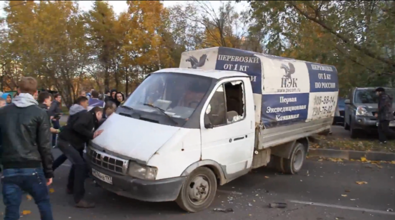 Rioters tipping over a delivery truck in Western Biryulyovo during recent unrest in the Moscow neighborhood. YouTube screenshot.