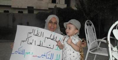 Suad Nofal with a child and one of her banners in Raqqa. Source: Suad Nofal´s facebook page.